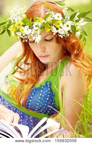 Portrait of a red-haired girl reading book outdoors