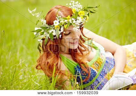 Portrait of a young in wreath reclining on grass with a book