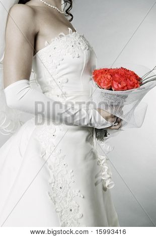 elegant bride with bunch of roses over grey background