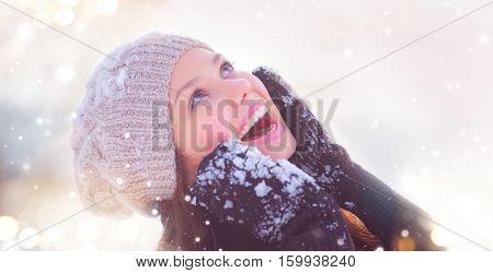 Winter young woman portrait. Beauty Joyful Model Girl touching her face skin and laughing, having fun in winter park. Beautiful young woman laughing outdoors. Enjoying nature, wintertime.