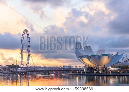 Singapore, Republic of Singapore - May 4, 2016: Panorama of Marina Bay with Artscience lotus flower museum, Flyer observation wheel and Helix bridge at sunset