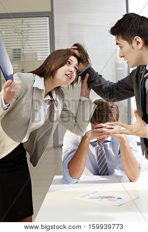 Furious businessman fighting with businesswoman in office