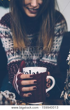 Crop shot of young woman in woolen sweater holding mug of hot drink and smiling.