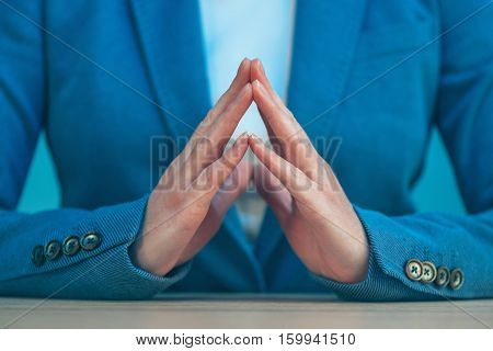 Steepled fingers of business woman as hand gesture sign of confidence self-esteem power and domination.