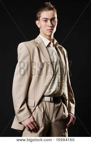 young businessman in beige suit over black background