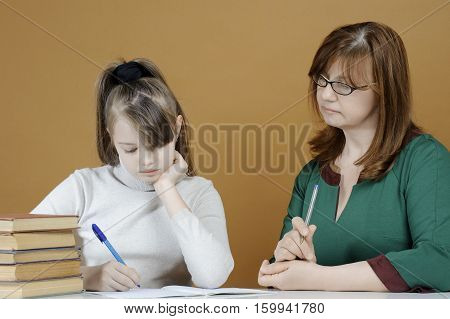 The Child Makes School Lessons Under The Supervision Of Her Mother..