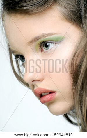 The face of a young girl with bright makeup on eyes.