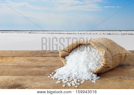 sea salt in bag. Crystals of salt in sack on table with salty lake in the background. Bag of sea salt produced on farm