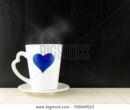 blue heart shape on white coffee cup on wooden table and wall, hot coffee with smoke, romantic coffee break