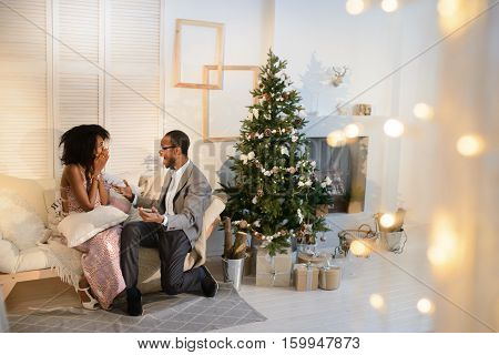 The handsome attractive afro-american man is making a great surprise to his girlfriend on the Christmas eve, she is very astonished and can't deal with emotions