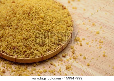 Closeup of Brown sugar in bamboo basket and on wooden table