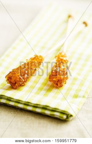 Brown amber sugar crystal on wooden stick on checkered napkin.