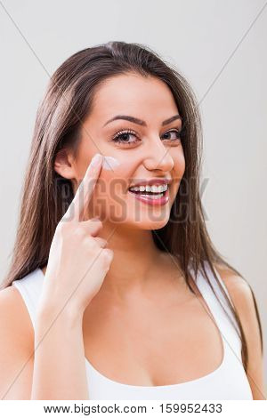 Portrait of young woman who is applying skin cream on her face.