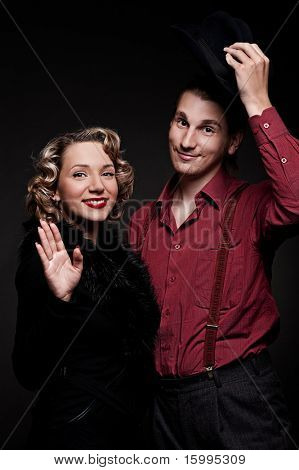 affable couple is greeting against dark background