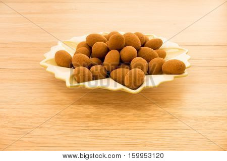 Closeup of Christmas almonds (Weihnachtsmandeln) coated with cocoa powder on a small plate. Isolated on gold brown wooden background with copy space.
