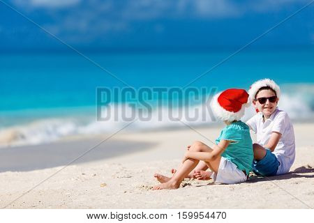 Kids in red Santa hats having fun at tropical beach during Christmas vacation