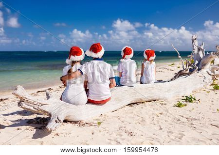 Back view of beautiful family wearing red Santa hats at tropical beach celebrating Christmas