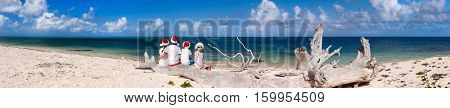 Panorama of beautiful family wearing red Santa hats at tropical beach celebrating Christmas