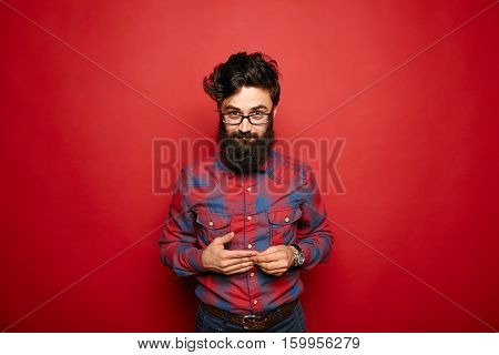 Single shy man with long beard in plaid shirt embarrassed expression over red background