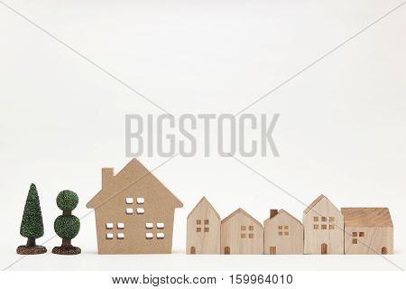 Miniature houses and trees on white background. Building blocks arranged in row.