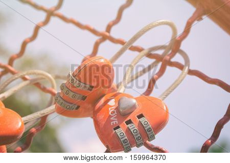 Couple heart love locker hanging on the fence