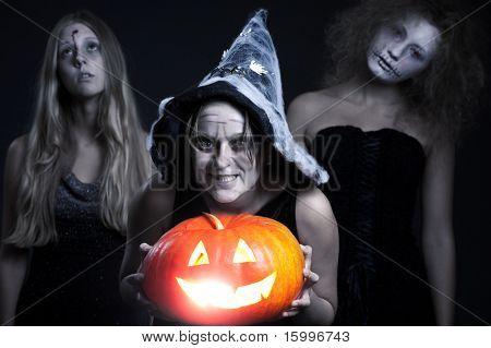 portrait of three halloween personages over dark background