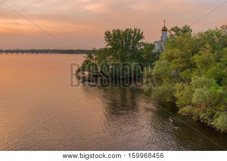 Landscape with an Orthodox church in sunset rays - Dnepropetrovsk city Ukraine.