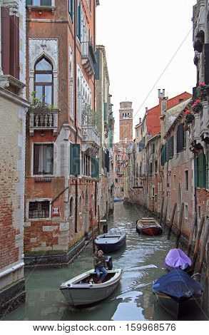 Venice Italy - November 23 2015: man is riding in motor boat by the narrow water canal in Venice Italy