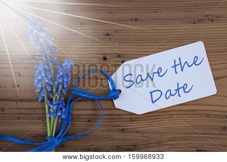Label With English Text Save The Date. Sunny Blue Spring Grape Hyacinth With Ribbon. Aged, Rustic Wodden Background. Greeting Card For Spring Season
