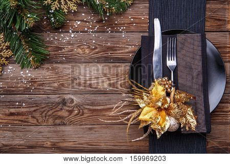 Christmas table place setting with black napkin, plate, fork and knife, decorated gold flower and christmas pine branches. Christmas holidays background.