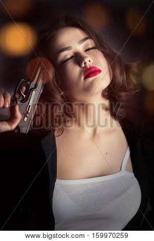 woman in black coat with gun on dark blurred background with lights, toned image