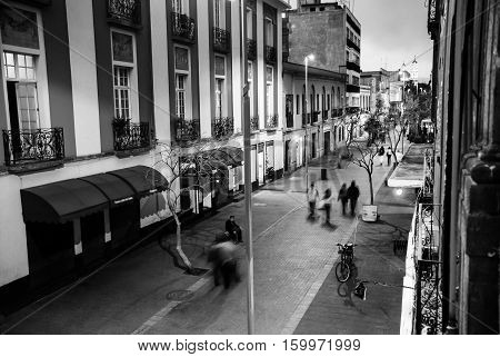 Mexico City is the capital of Mexico. Nightlife in Mexico City. Streets of the center with blurred people bars restaurants and cafes. Black and white