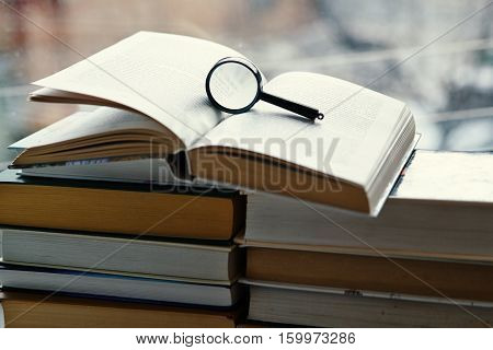 Open hardcover book, magnifying glass hard cover