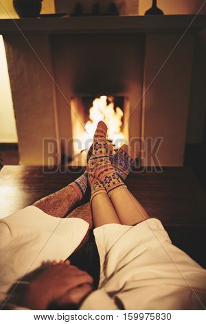 Couple in socks and robs sitting at fireplace