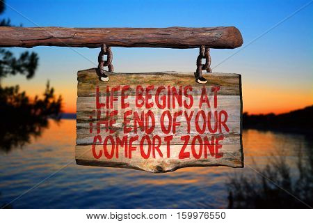 Life begins at the end of your comfort zone motivational phrase sign on old wood with blurred background