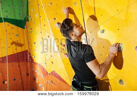 Harmony and power. Enthusiastic handsome young man spending time in climbing gym while climbing up the wall and using insurance ropes.