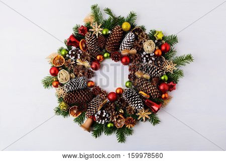 Christmas wreath with fir branches pine cones and jingle bells. Christmas background with baubles rustic ornaments and dried orange slices.