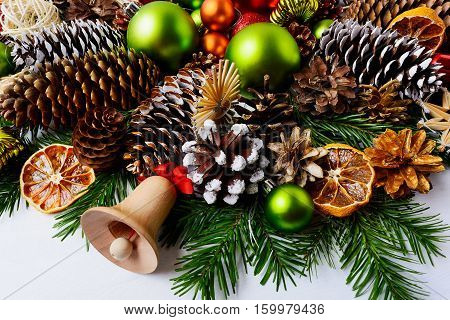 Christmas decoration with fir branches pine cones and dried oranges. Christmas background with baubles rustic ornaments and wooden jingle bell.