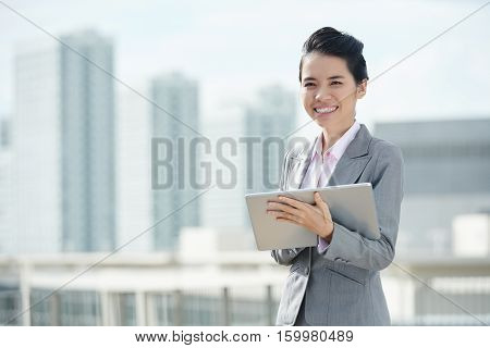Pretty female business executive with big tablet in her hands