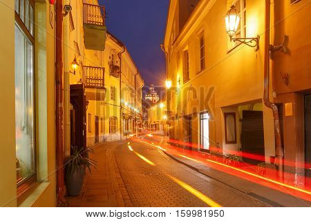 Picturesque Street and luminous track from the car at night in Old Town of Vilnius, Lithuania, Baltic states.
