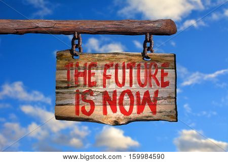 The future is now motivational phrase sign on old wood with blurred background