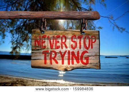 Never stop trying motivational phrase sign on old wood with blurred background