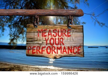 Measure your performance motivational phrase sign on old wood with blurred background