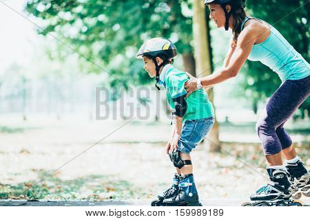 Mother teching son roller skating in park