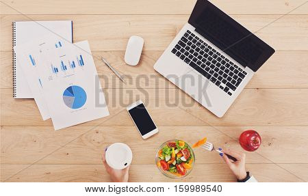 Woman eat business lunch at working place. Businesswoman's hands with fork and glass on wooden desk in office. Healthy diet food, vegetable salad with apple near laptop and papers. Top view, flat lay
