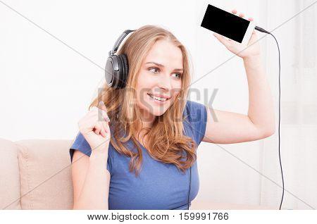 Woman Holding Up Smartphone Listening To Headphones