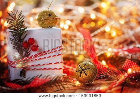 Christmas Decoration gift box and gold jingle bells with branch fir and sparkle. Holiday greeting card.