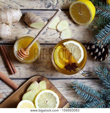 Hot tea with lemon, honey, ginger and anise on a wooden rustic background.. Healthy drink. Hot winter beverage concept.