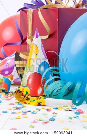 Birthday party with a gift or present box, party hats, horns or whistles, balloons, confetti and str