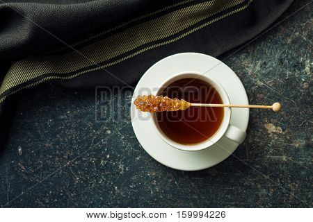 Brown amber sugar crystal on wooden stick and tea cup. Top view.